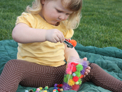 Stephanie Roberts, MA, OTR/L, Girl playing with pom pom toy
