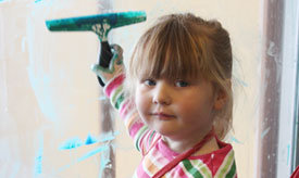 Girl holding paint scrapper, photo